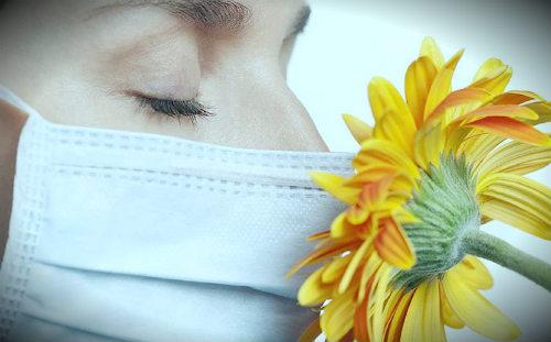 нюхает цветок в маске