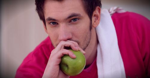 парень держит яблоко
